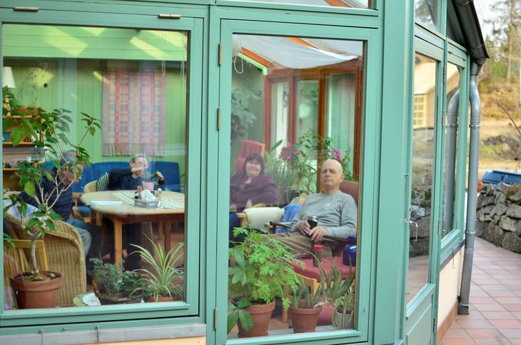 Mennersker som sitter i en vinterhage med grønne planter